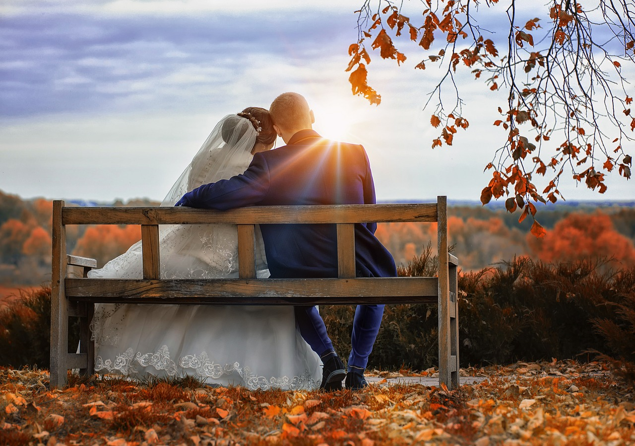 A couple sat on a bench on their wedding day